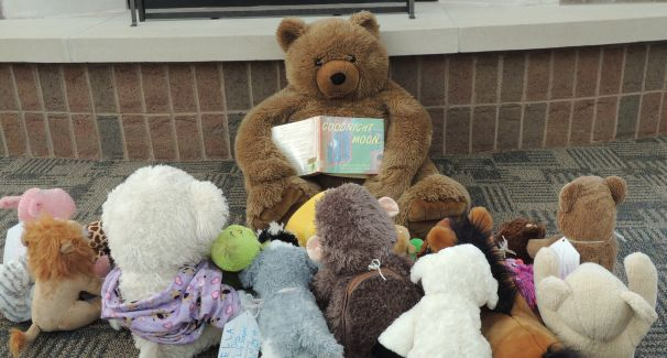 Giant teddy bear reading to stuffed animals